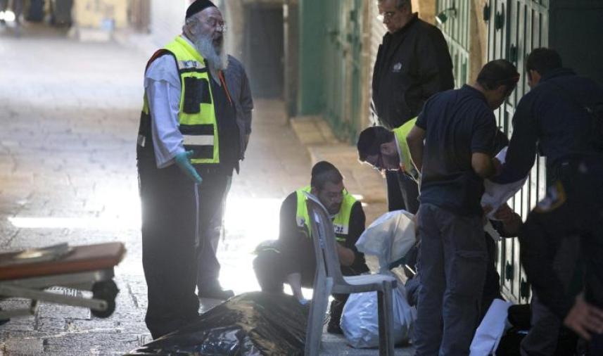 أعضاء فريق أمني إسرائيلي ينقلون جثة شهيد فلسطيني قُتل بعد طعنه شرطيا بالقدس القديمة